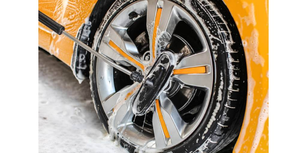 brush washing yellow car wheel