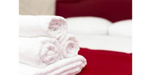 clean folded towel on hotel bed