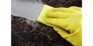 wiping grease clean with yellow sponge