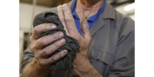 factory worker (man) wiping grease off his hands