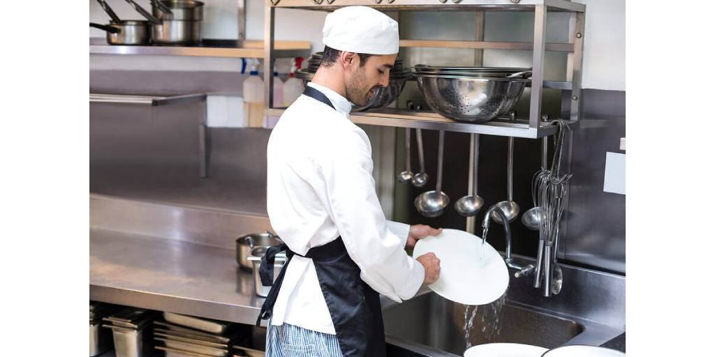 chef in black apron washing a white plate