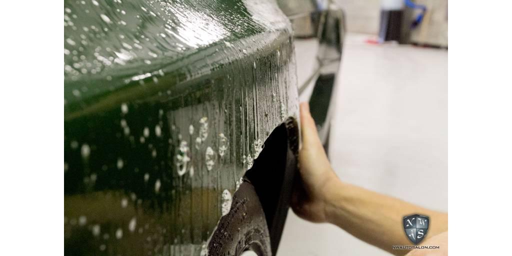 hand washing car around wheel