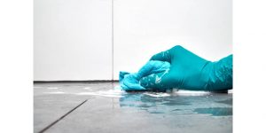 teal glove with blue cloth hand washing floor tiles
