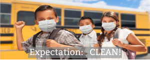 school children with mask in front of a school bus