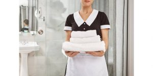 hotel housekeeper holding clean white towels