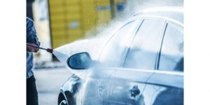 man spraying car with pressure washer
