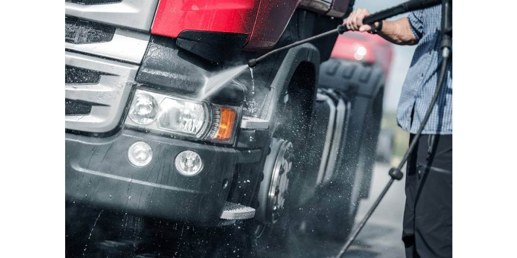 man power washing a truck